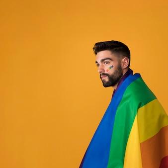美しい同性愛者の虹の旗を包む