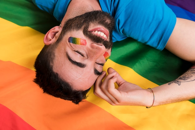 Перевернутый улыбающийся человек лежит на разноцветном флаге лгбт