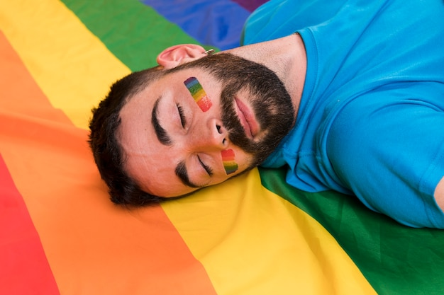 Молодой человек лежит на разноцветном флаге лгбт