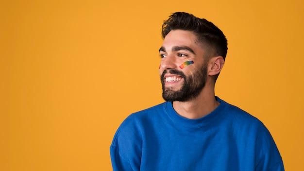 Улыбающийся молодой человек с лгбт радугой на лице