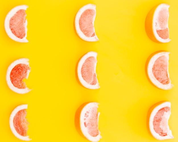 Ломтики грейпфрута на желтом фоне