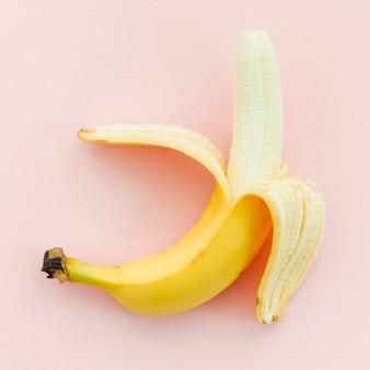 ピンクの背景に半分皮をむいたバナナ