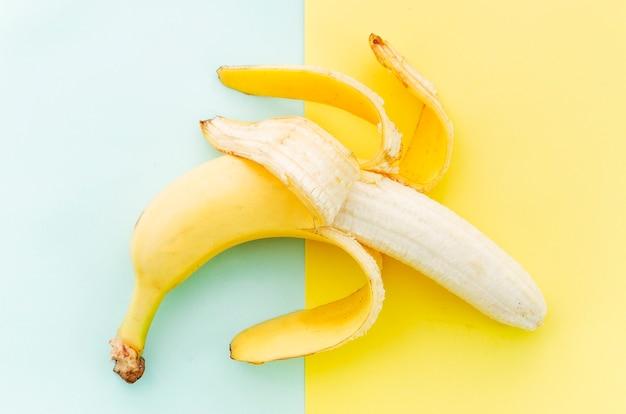 Очищенный банан на цветной поверхности
