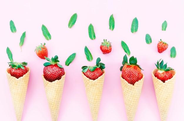 明るい背景にアイスクリームのワッフルコーンのイチゴ