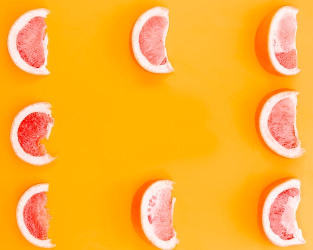 オレンジ色の背景上のグレープフルーツのスライス
