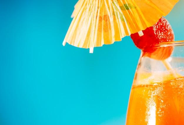 オレンジ色の飲み物を傘で飾られたガラスのイチゴ