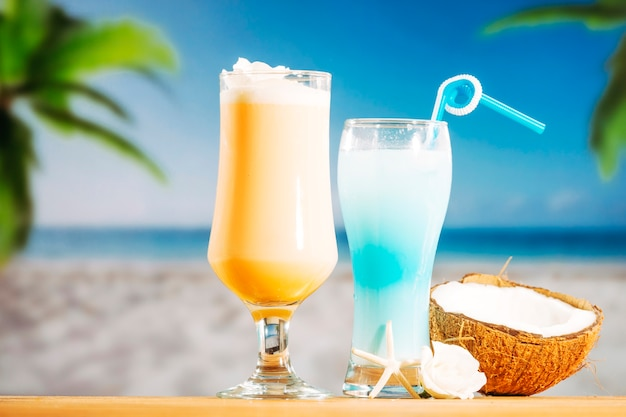 柔らかい黄色の冷凍ブルーの飲み物とひびの入ったココナッツ