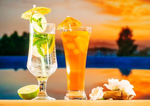 Свежие апельсиновые напитки с кусочками лайма, мяты, кубиками льда и белыми цветами