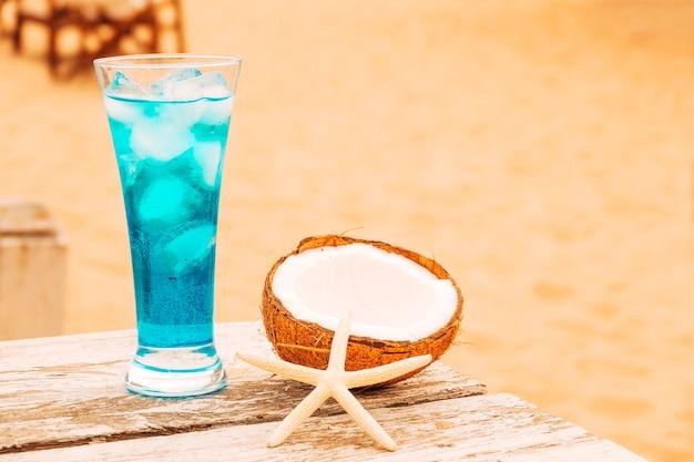 冷たい青い飲み物とひびの入ったココナッツ木製テーブルのガラス