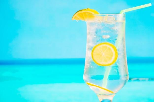 スライスしたレモンとわらの冷凍飲み物のガラス