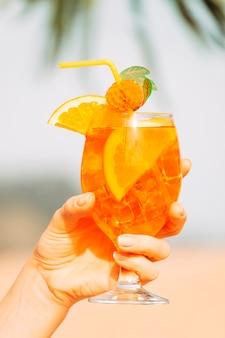 Декорированный стакан охлажденного апельсинового напитка в руке