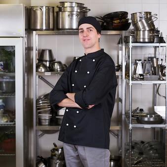 制服と調理器具のあるキッチンシェフ