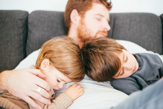 ソファの上のかわいい息子とスヌーピングお父さん