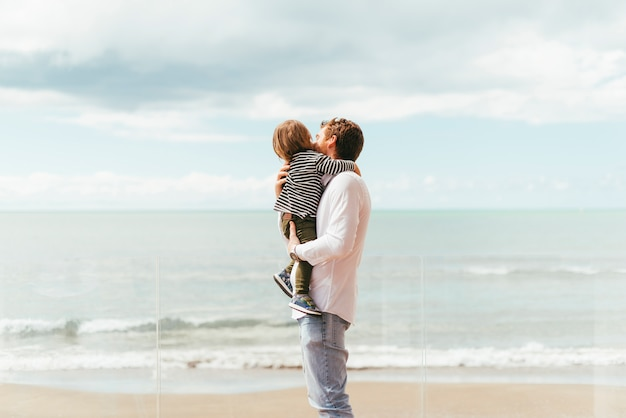 海岸で幼児の息子を持つ父親