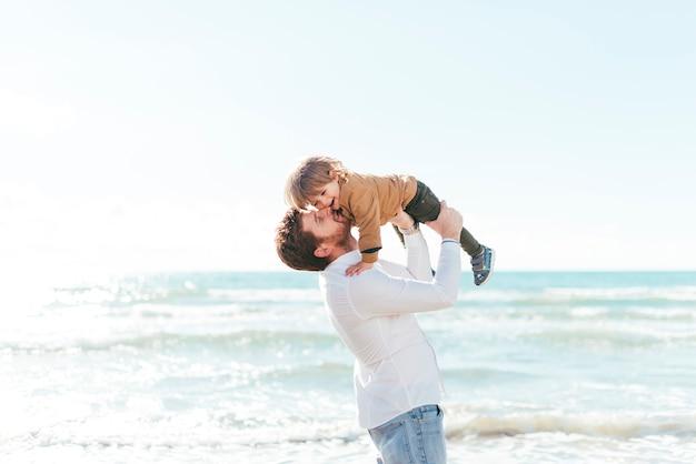 Мужчина поднимает мальчика на берегу моря