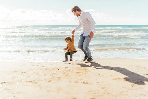 海岸でジャンプの幼児を持つ男