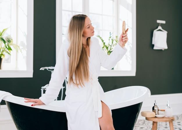 Блондинка позирует в ванной с банным халатом