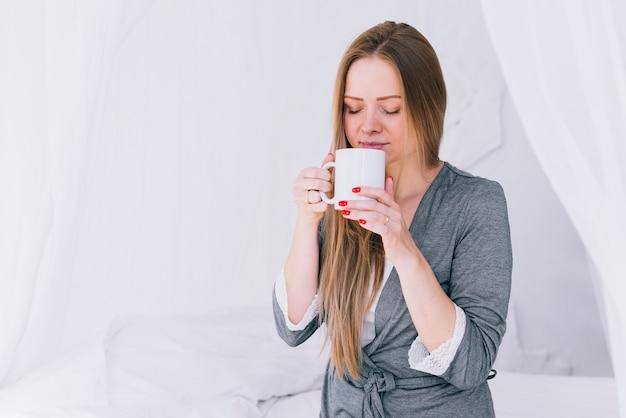 ベッドでコーヒーを飲んでいる女の子