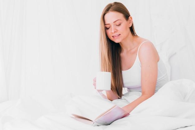 ベッドの上の本とコーヒーを飲んでいる女の子
