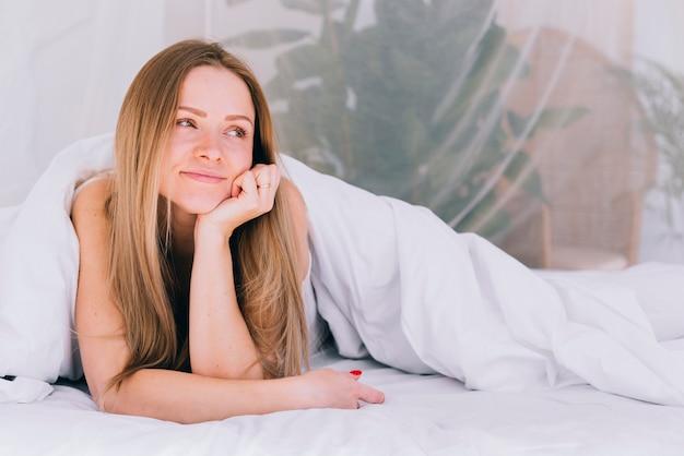ブロンドの女の子がベッドの上でポーズ