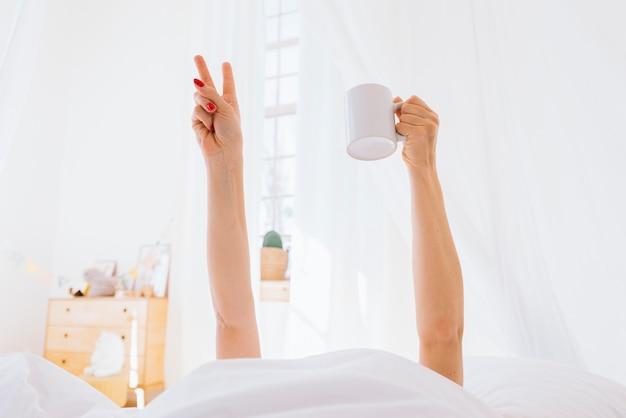 朝のコーヒーを飲んでいるブロンドの女の子