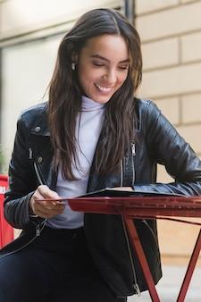 屋外カフェでメニューカードを読んでファッショナブルな笑顔若い女性