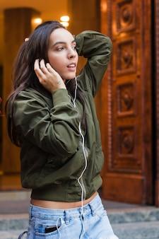 ファッショナブルな若い女性がイヤホンで音楽を聴く