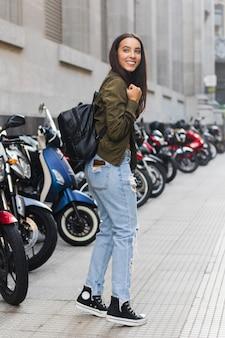彼女のバックパックが駐車場の前に立っている若い女性を笑顔