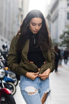 Портрет молодой женщины, застегивающей куртку на улице