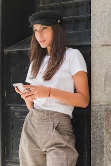 Стильная молодая женщина в черной кепке держит мобильный телефон в руке, глядя