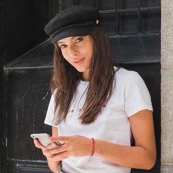 Портрет молодой женщины, глядя на камеру с помощью мобильного телефона