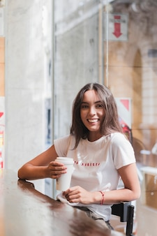 使い捨てのコーヒーカップを手で押しカフェに座っている若い女性の笑みを浮かべてください。