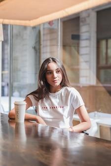 テーブルの上の使い捨てのコーヒーカップとカフェに座っている若い女性の肖像画