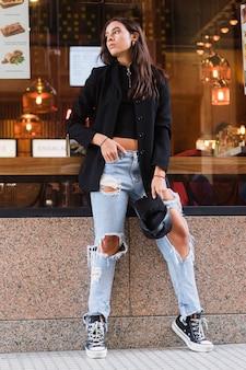 手に黒い帽子を保持している破れたジーンズを着てレストランのガラスにもたれて若い女性