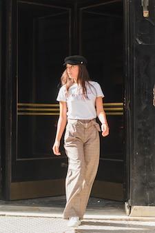 通りを歩いて彼女の頭の上のキャップを持つスタイリッシュな若い女性