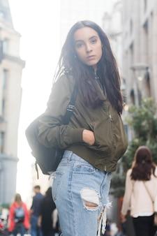 カメラ目線のポケットに彼女の手を持つ若い女性の肖像画
