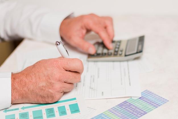 Бизнесмен с помощью калькулятора