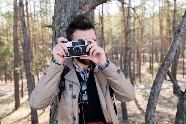 若い男が森の中のカメラで写真を撮影