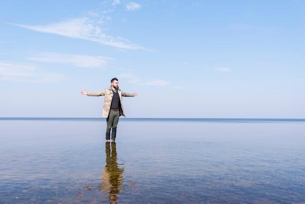 浅い海の水の中に彼の手の立っている広げて一人の若い男