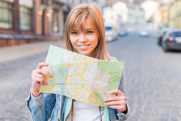 Портрет улыбающегося женского туриста, стоящего на улице, показывая карту