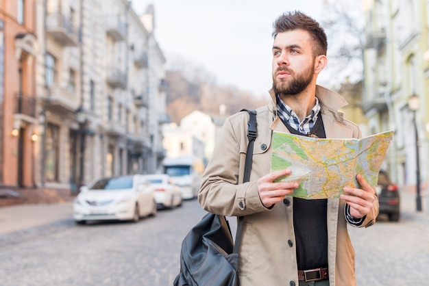 離れて見て手で地図を持って通りに立っている彼の肩にバッグを持つ若い男性観光客