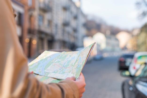 街の通りに手で立っているマップを保持している男性の旅行者のクローズアップ
