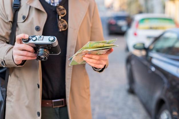 男性旅行者の手で地図とビンテージカメラを保持