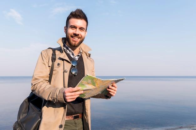 手で地図を持って海の前に立っている男性の旅行者の肖像画を笑顔