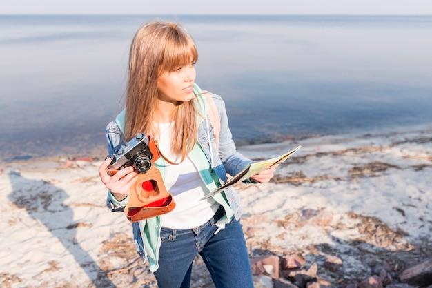 ビンテージカメラと地図を手に持った金髪の若い女性がビーチに立っています。