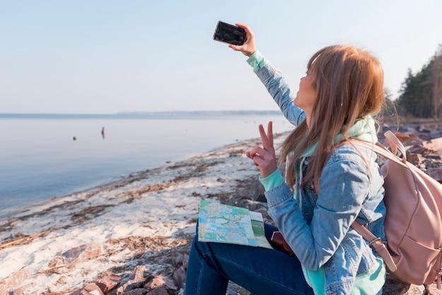 Женский путешественник, сидя на пляже, принимая селфи на мобильный телефон