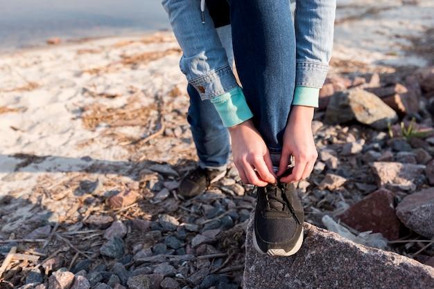 女性旅行者のビーチで靴ひもを結ぶ