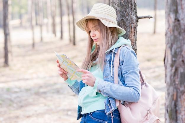 Женский путешественник с ее рюкзаком стоит под деревом и смотрит на карту