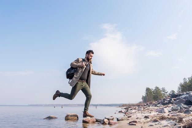 湖の石の上を走っている彼のバックパックを持つ若い男性旅行者