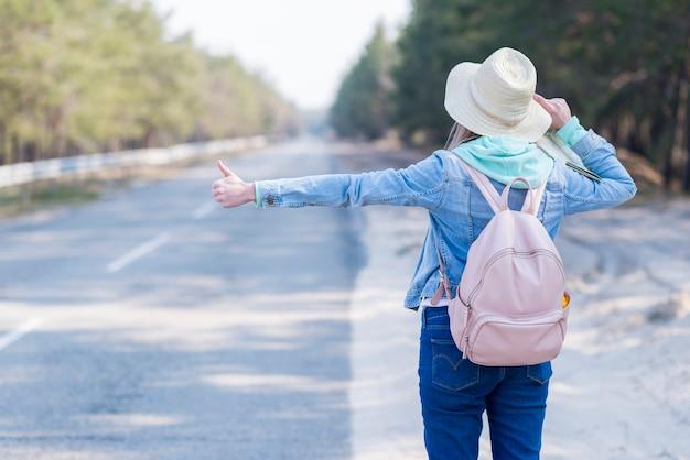 Вид сзади женщины с шляпой и рюкзаком автостопом на сельской дороге